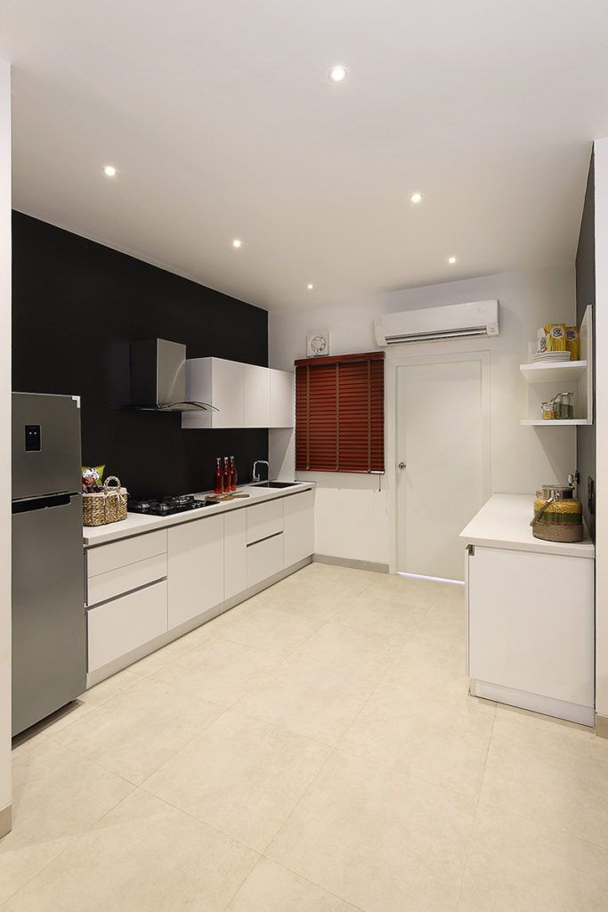 a well designed kitchen equipped with a fridge, chimney and sleek cabinets for everyday use.
