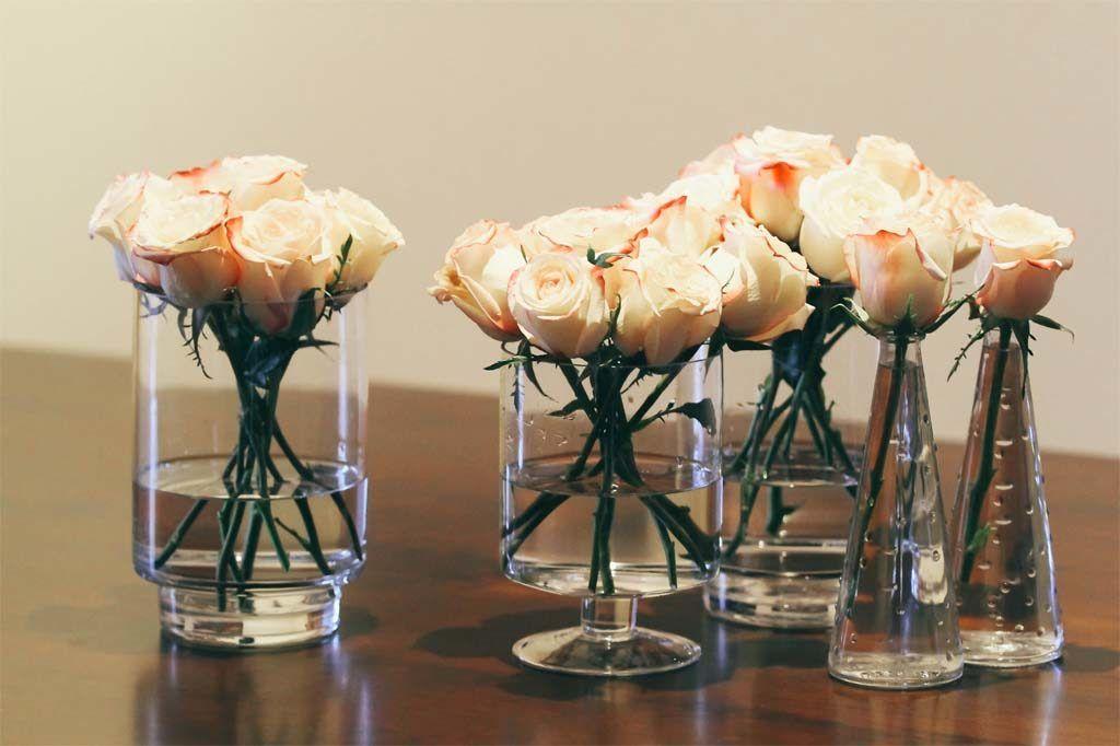 rose flower arrangements in glass bottles