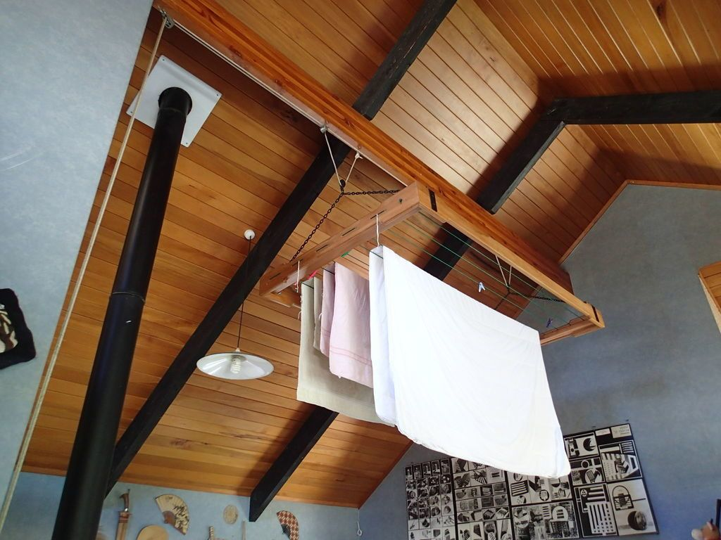Mount the pulley controlled rack to a ceiling to dry clothes indoors.
