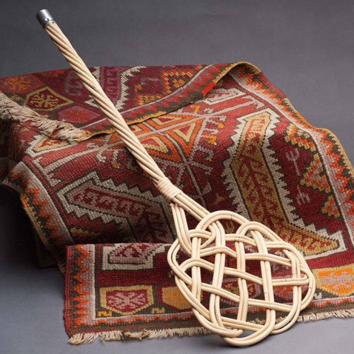 Use carpet beater to clean Persian rug.