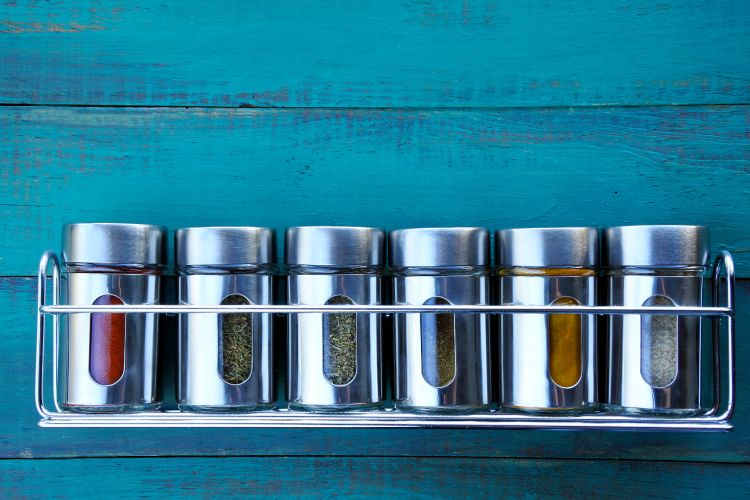 Wall mounted spice racks can help organize spices in a small kitchen