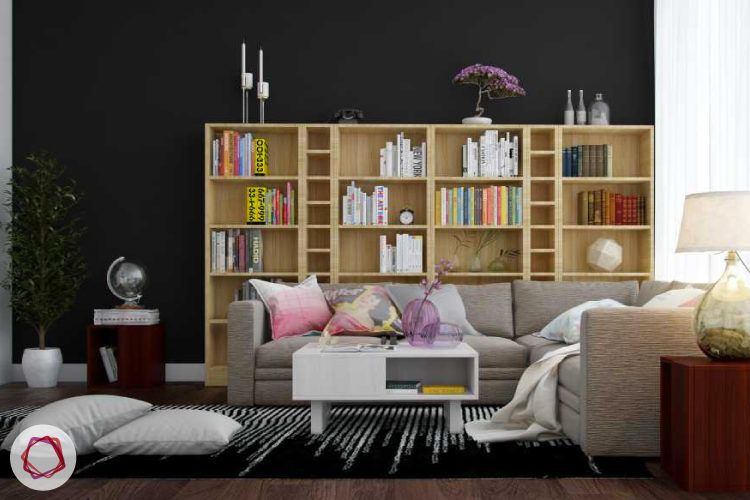 Neutral themed home library with large bookshelf and L shaped sofa.
