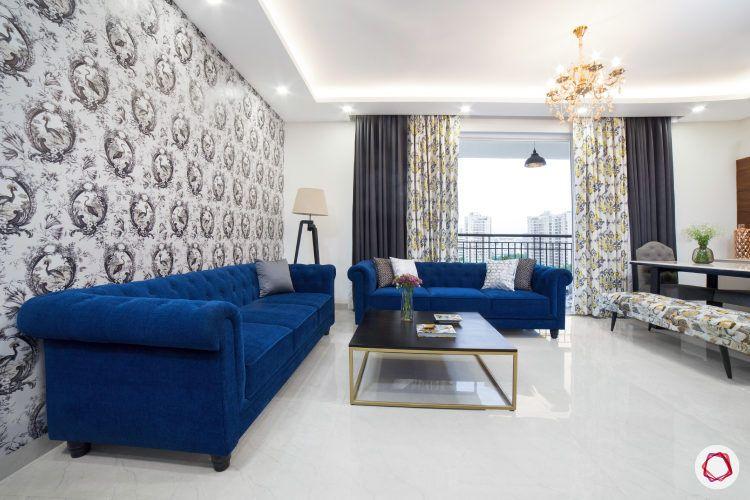 best interior design-living room-ornate chandelier-blue sofa-wallpaper