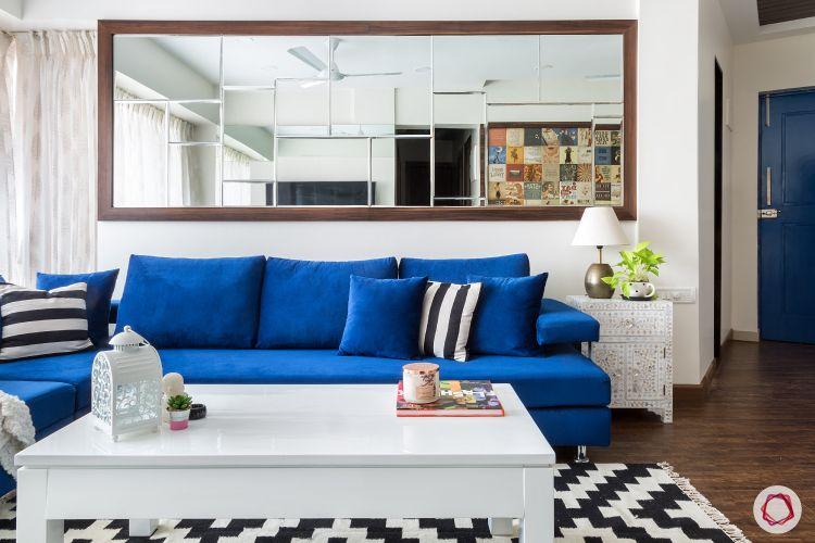 parineeti chopra-blue-sofa-mirror-coffee-table-white-rug-wooden-floor