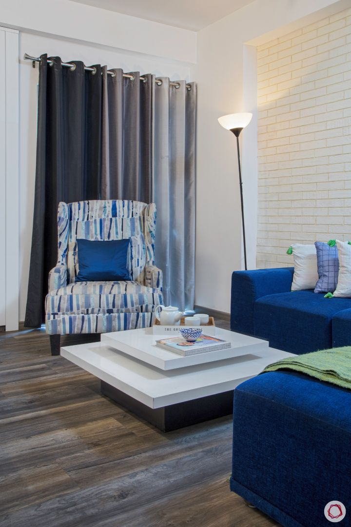 New house design-entertainment room-blue sofa-white exposed brick accent wall-floor lamp-coffee table