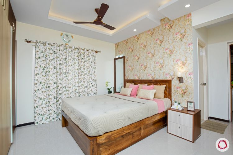 interior master bedroom with wood furniture and floral wallpaper