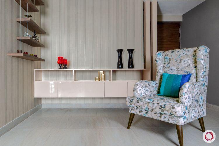 3bhk flat_living room-floral-armchair-shelf-wallpaper