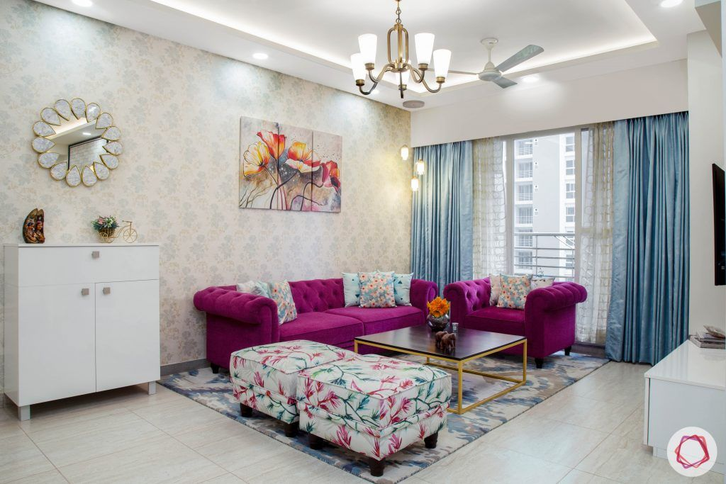 Cleo county noida_living room with purple colour sofa and floral ottomans