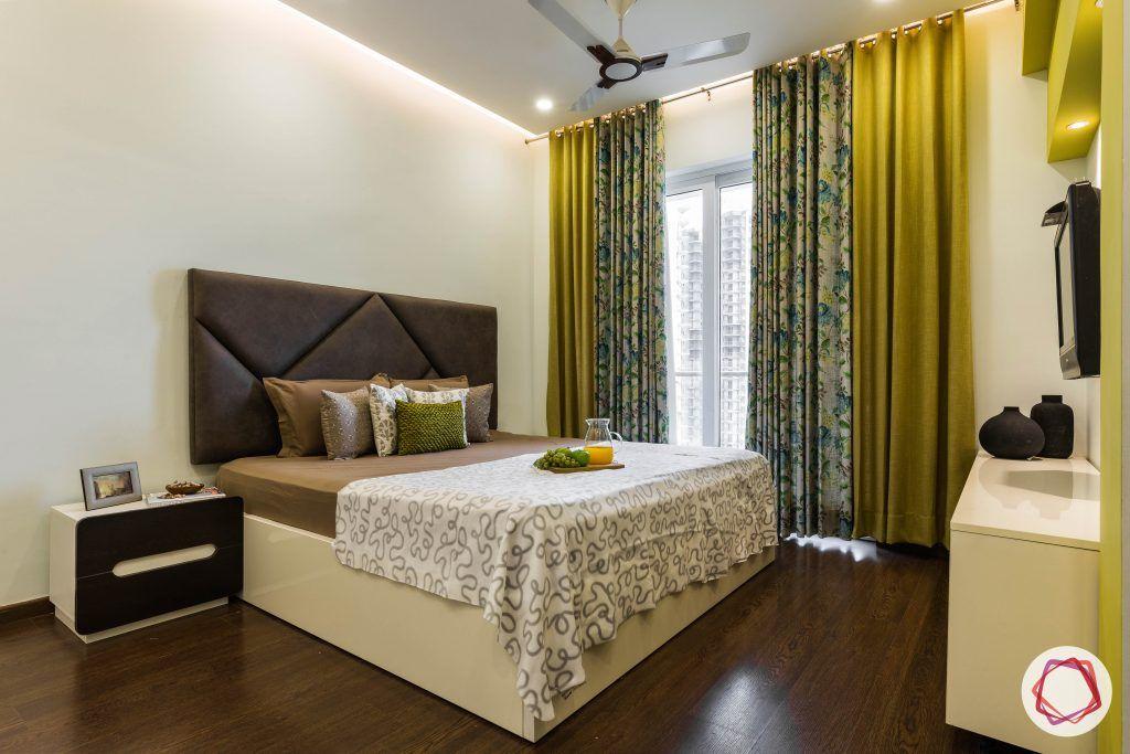flat interior design-master bedroom-grey headboard-bedside table-wooden flooring-mustard curtains