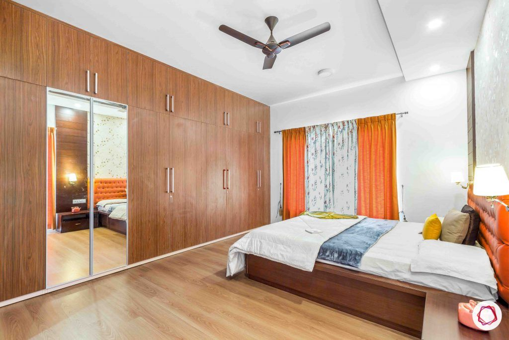 sobha forest view-master bedroom-rust orange-wooden tones-laminate finish wardrobe-wooden flooring