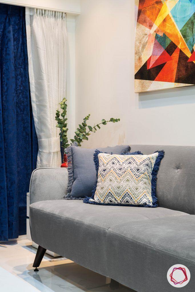 house-renovation-living-room-compact-grey-sofa-white-curtains-white-tiles-wall-art