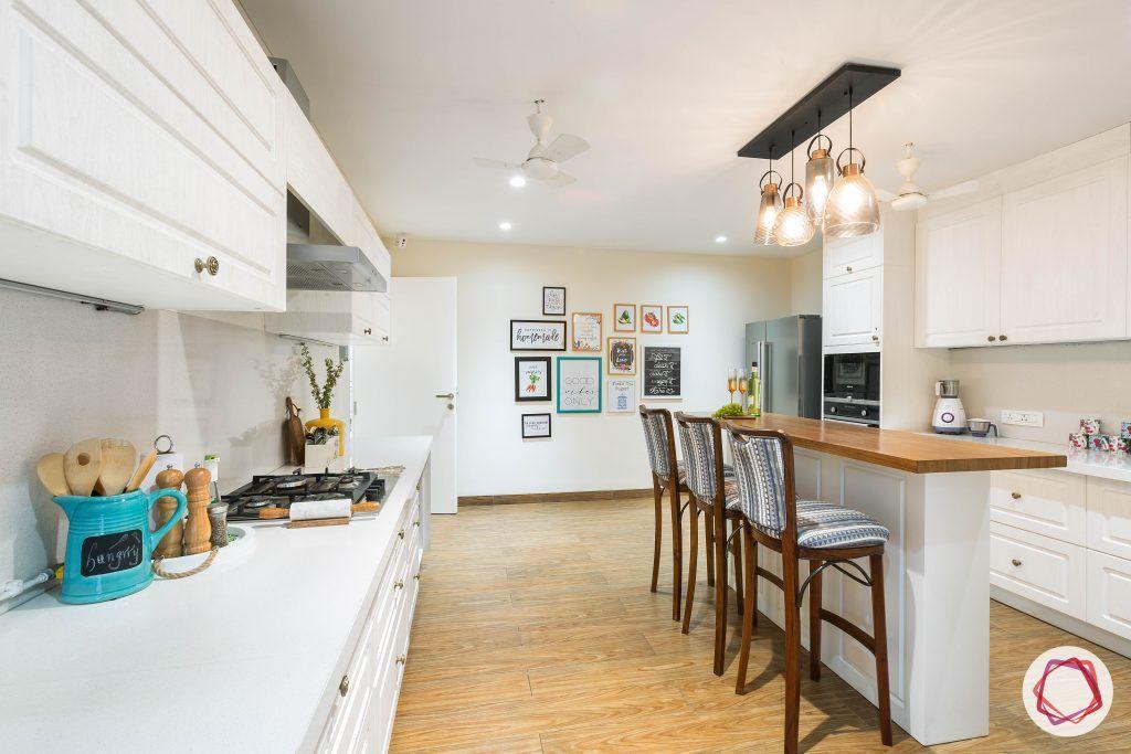 4bhk house plan-white kitchen designs-quartz countertops-white countertops-island kitchen designs-breakfast counter in kitchen-wooden flooring designs-high bar chairs
