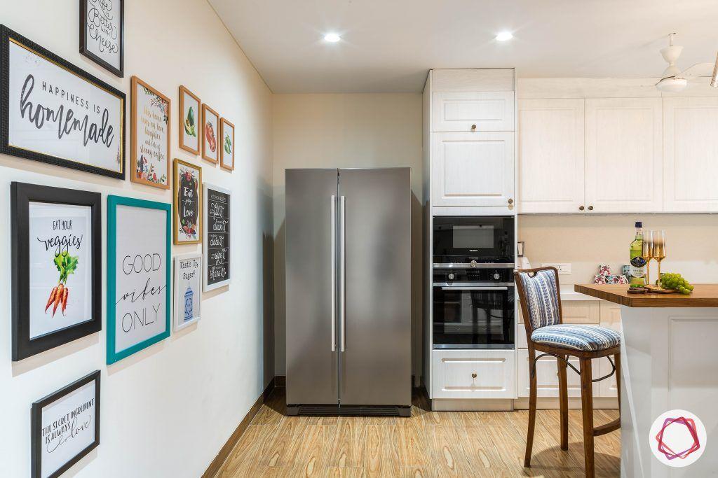 4bhk house plan-white kitchen designs-quartz countertops-white countertops-island kitchen designs-breakfast counter in kitchen-wooden flooring designs-kitchen gallery wall