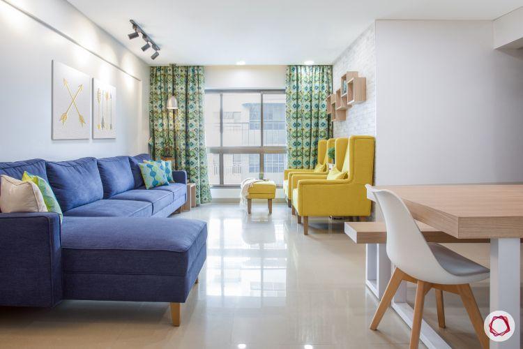 godrej homes-mumbai home-living room-bright living room-yellow chairs-blue sofa-track lights-white walls