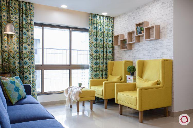 godrej homes-mumbai home-living room-yellow chairs-display shelves-exposed brick wallpaper-printed curtains