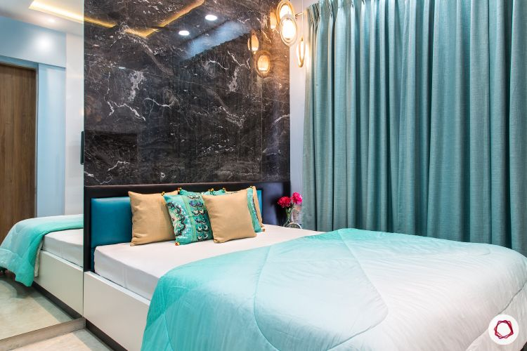 best interior designers in mumbai-bedroom-marble tiles-accent wall-blue curtains