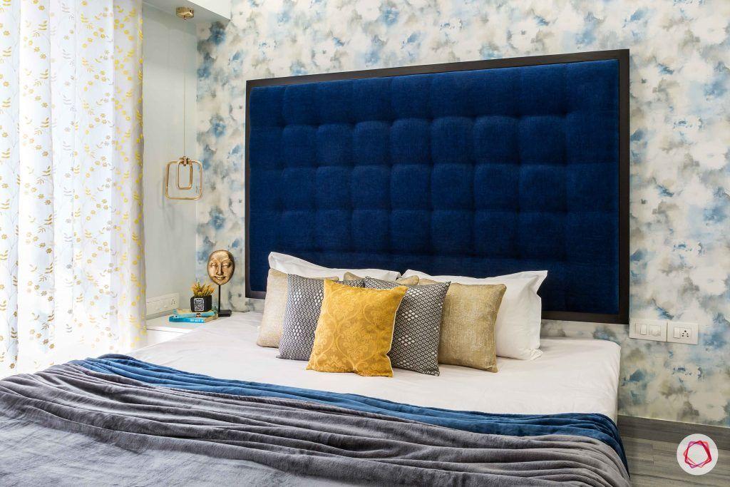bedroom-blue-headboard-floral-wallpaper-pillows