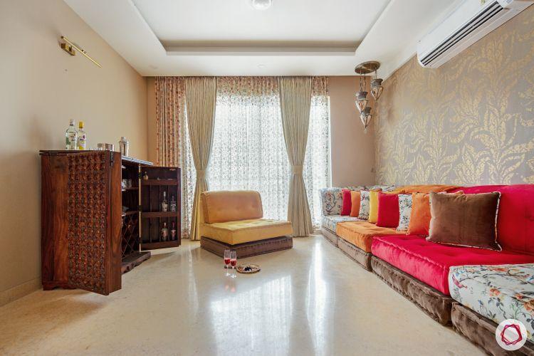 celebrity-homes-low-floor-seating-yellow-orange-bar-unit-window-curtain