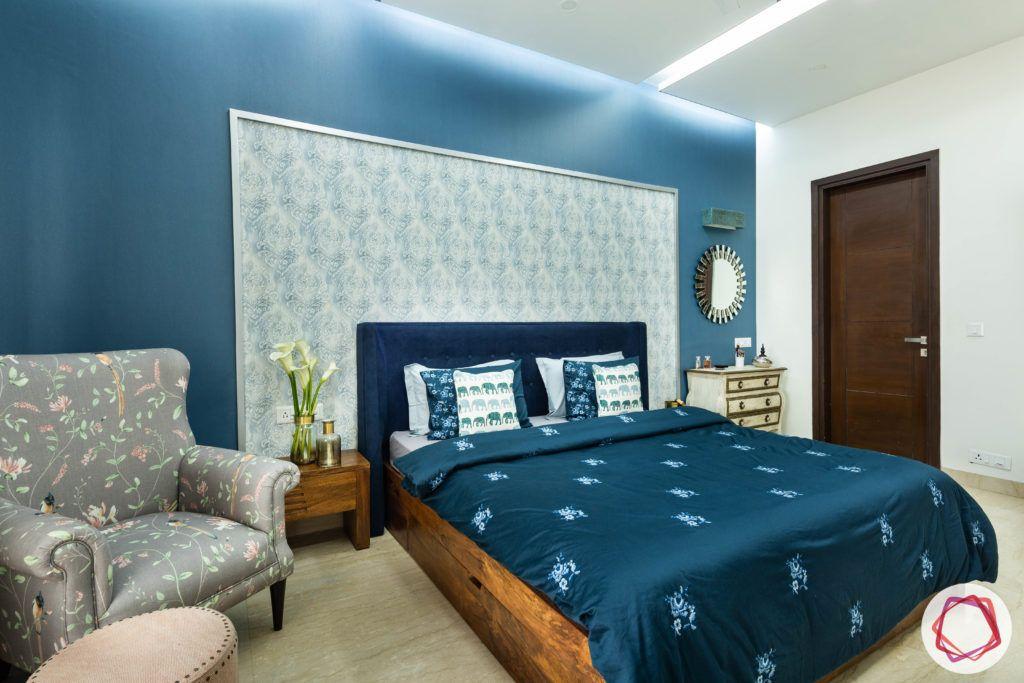 blue-wall-sheet-headboard-floral-armchair