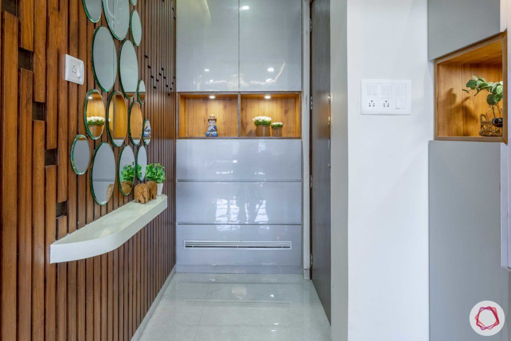 2 bhk flat interior-entrance-foyer-mirrors-wooden panels-storage-glossy finish