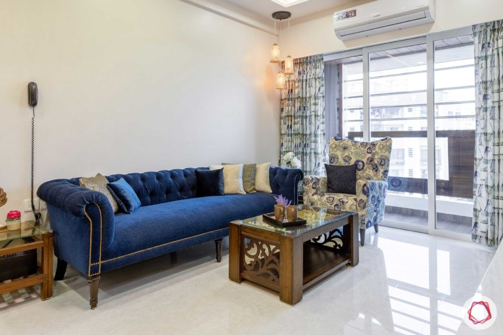 2 bhk flat interior-living room-blue sofa-printed accent chair-wooden centre table