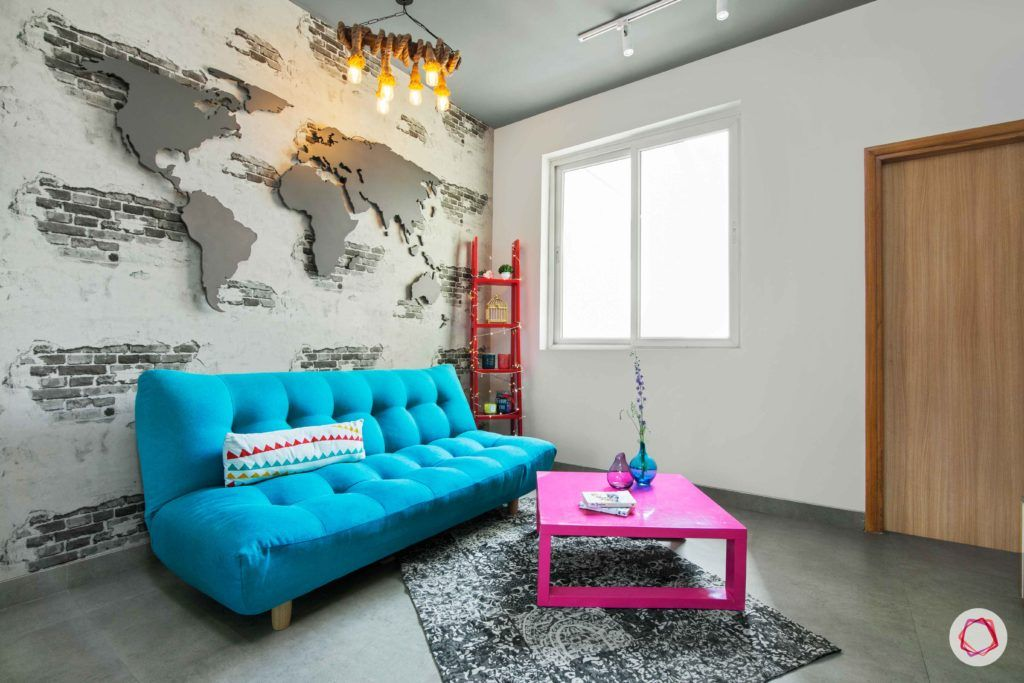 tdi ourania_blue sofa cum bed_pink table_exposed brick wall