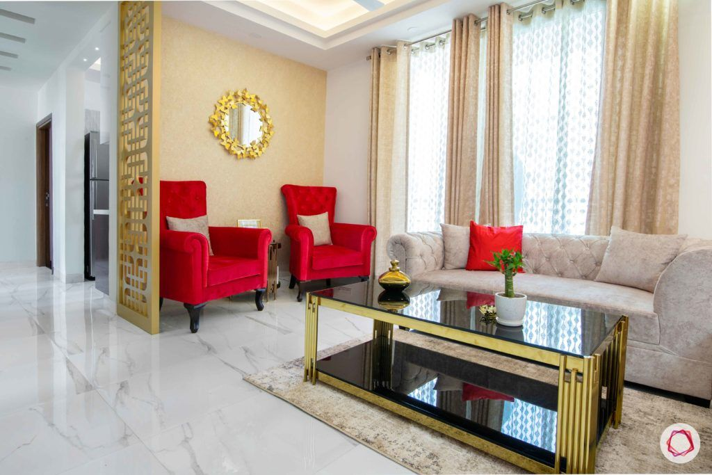 tdi ourania_living room_red accent chairs_golden mirror_golden wallpaper