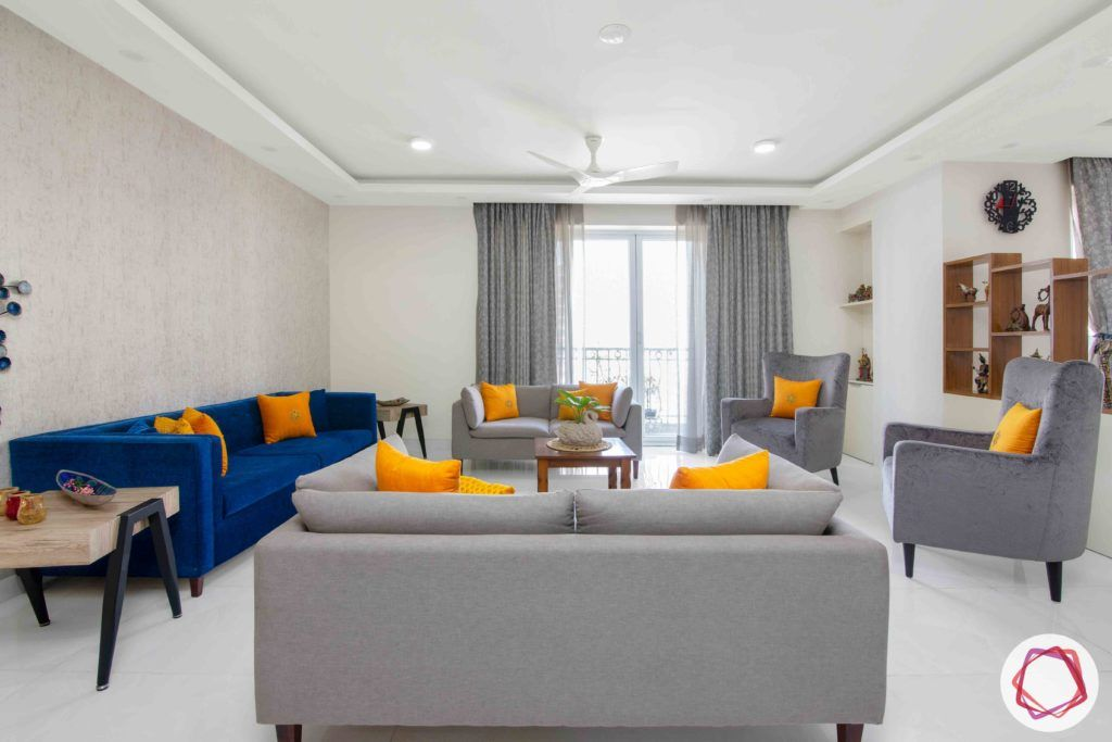 Shipra Srishti-living-room-blue-yellow-sofa-pillows-floral-accent-curtains