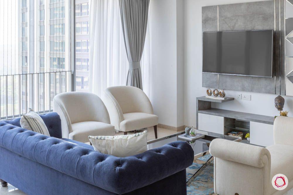 oberoi goregaon-living room-blue sofa-white chairs-laminate tv unit