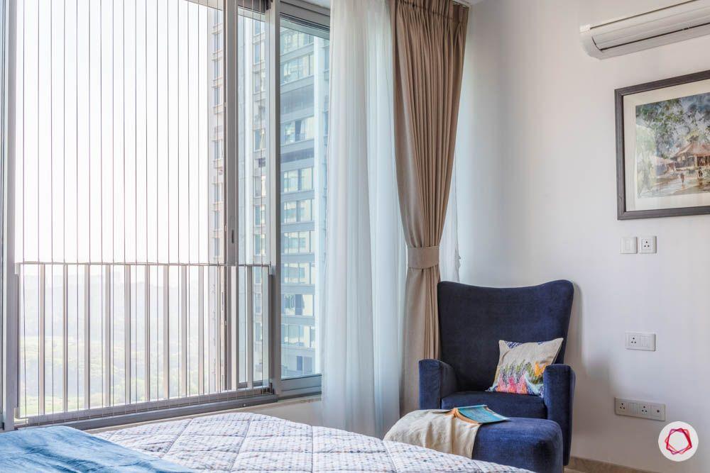 oberoi goregaon-master bedroom-reading corner-blue wing chair-footrest