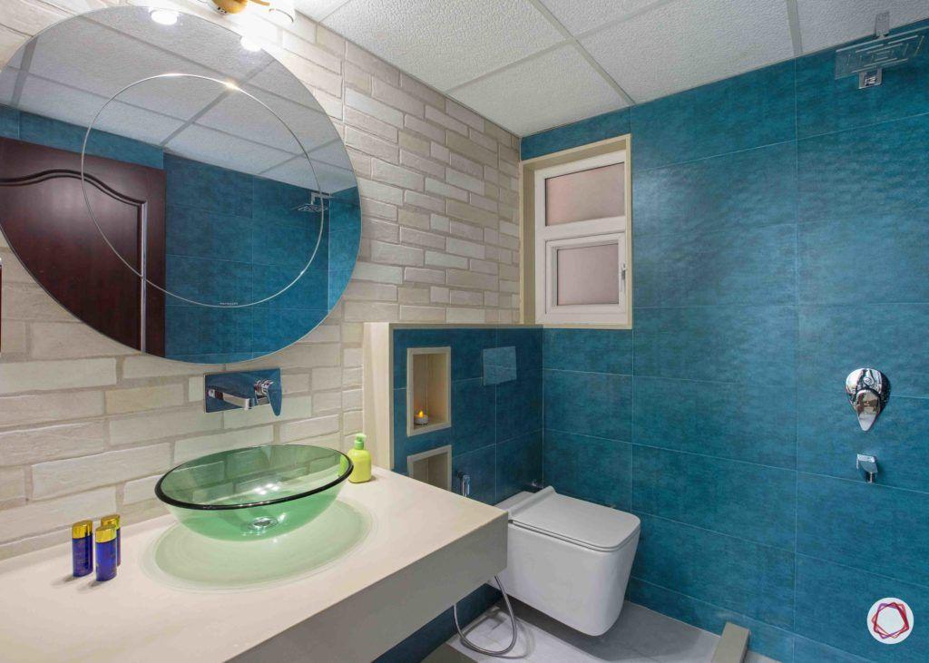 bathroom-circle-mirror-brick-tiles-blue-wall-storage-cabinets