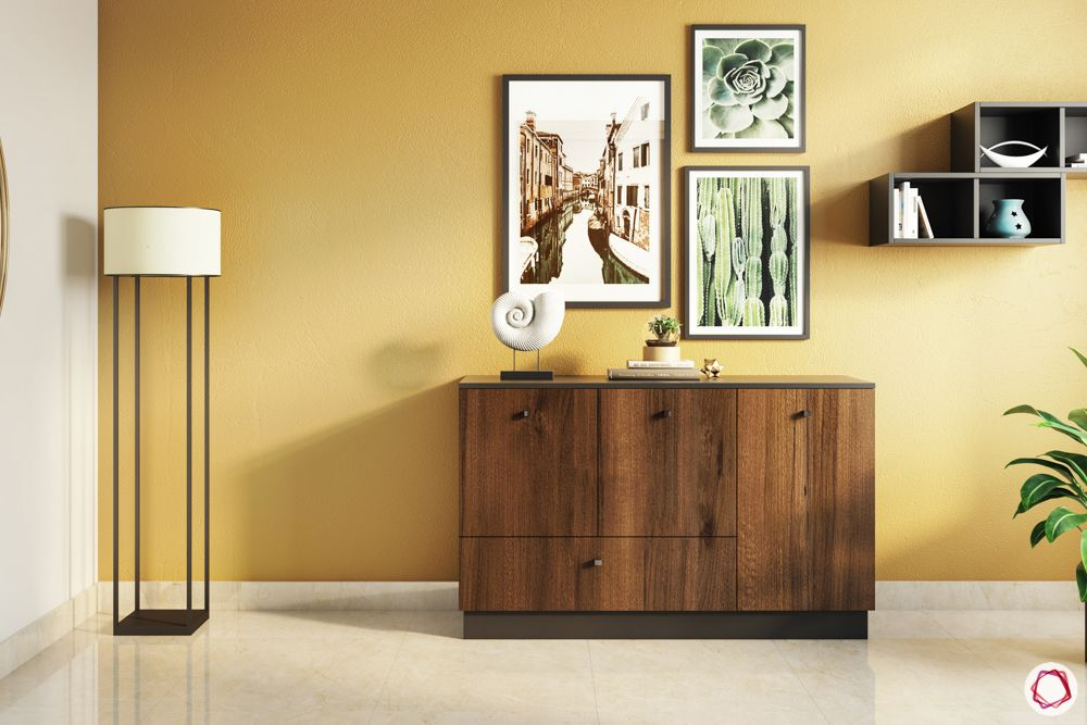 foyer-area-design-wooden console table-yellow wall-frames-floor lamp