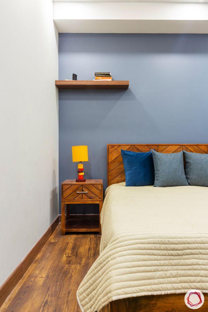 grey walls-oak wood bed-table lamp