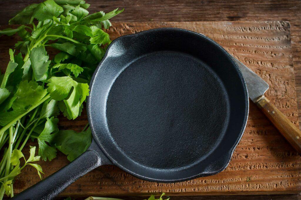 cast iron pan-coriander-knife-wooden-board