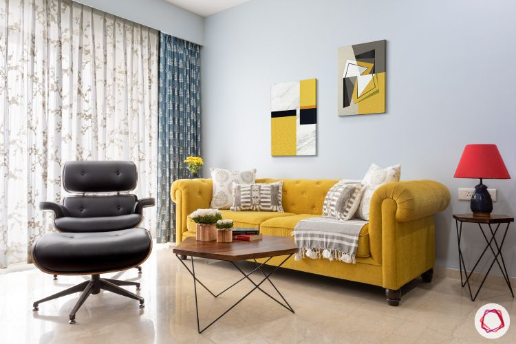 yellow sofa-popular sofa colors-white cushions-industrial table-wall frames