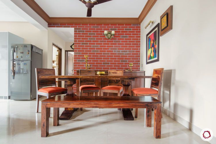 cream walls and dark wood furniture-wooden dining table-brick wall-wall art-wooden bench