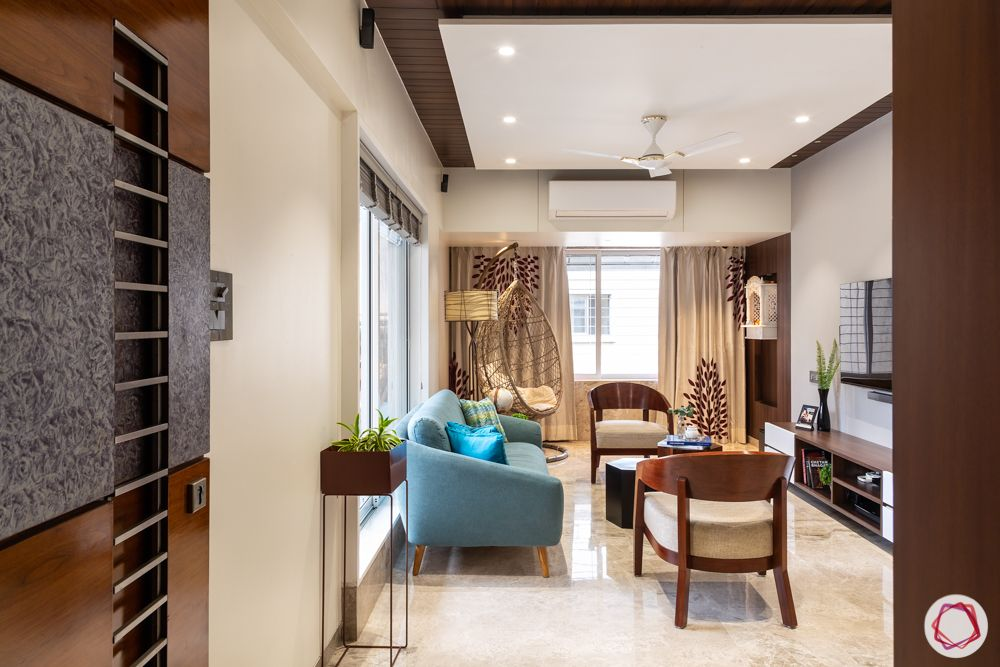 home renovation mumbai-Entrance-blue sofa-wooden chairs-window designs