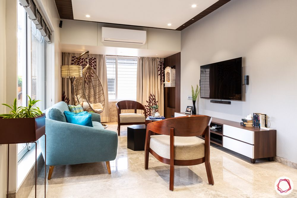 home renovation mumbai-blue sofa-tv unit-wooden chairs-ceiling designs