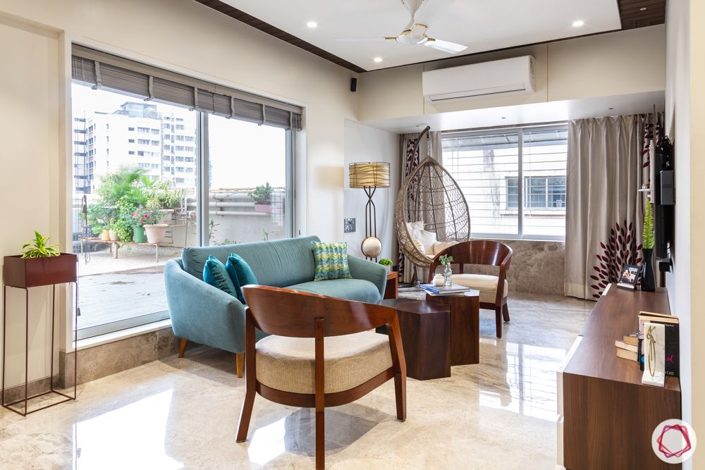 home renovation mumbai-blue sofa-wooden chairs-tv unit-swing chair