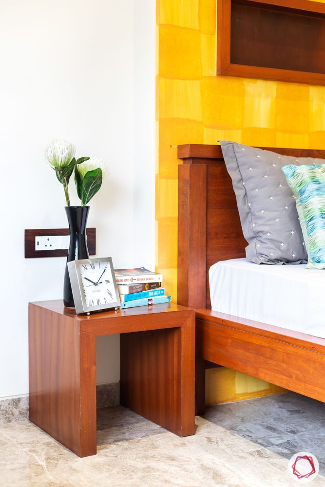 home renovation mumbai-wooden bedside table-wooden bed-yellow wall
