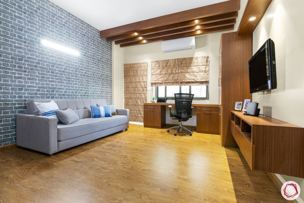 ardee city-wooden rafter ceiling-wooden multifunctional unit-study table-bookshelf-pooja unit-tv unit-sofa bed-exposed brick accent wall