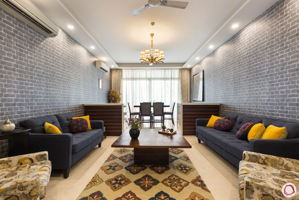 4 bhk apartment-living room-grey wall-yellow cushions-carpet-dining room-lighting