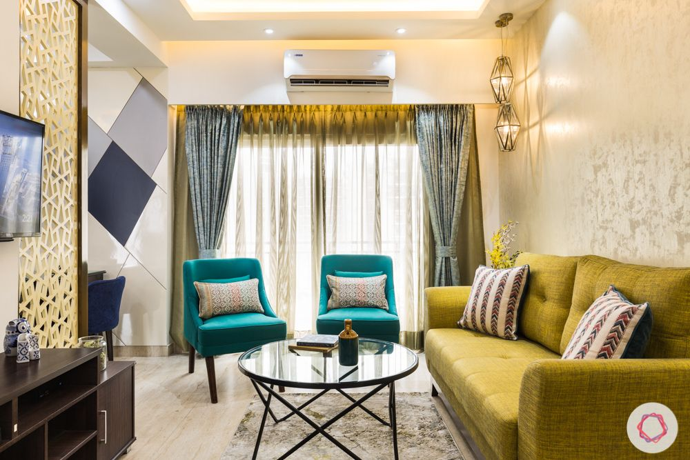 low budget home design-yellow couch-green arm chairs-jaali partition-pendant lghts