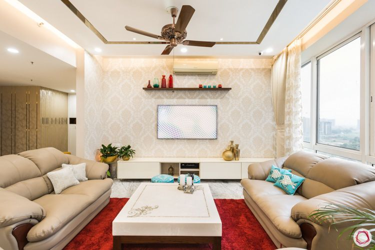 bhk flat-gold motif wallpaper-tv unit designs-false ceiling and lighting-red rug-coffee table