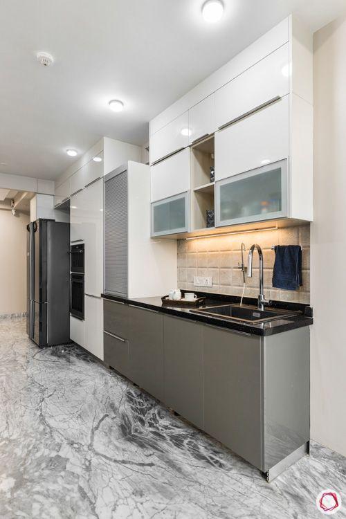 4 bhk flat-kitchen sink-white overhead cabinets-grey base cabinets-tiled backsplash