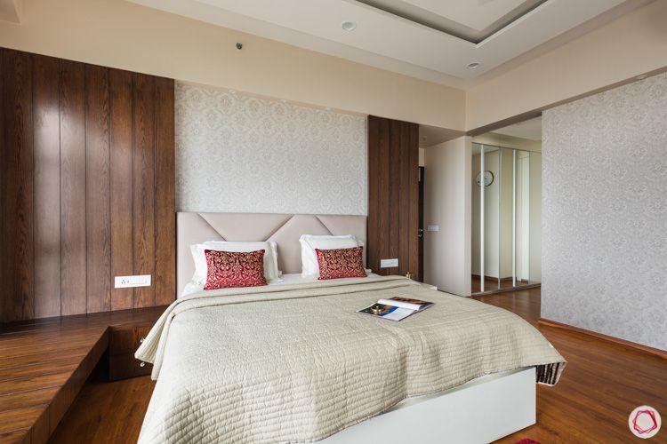 wooden panelling-beige headboard-gold motif wallpaper-wooden bay seating-walk-in wardrobe-mirror wardrobes
