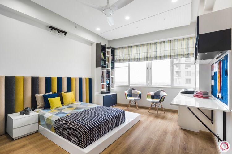 4 bhk flat-cushioned headboard-multi-coloured headboard-low bed designs-patchwork armchairs-bookshelf designs