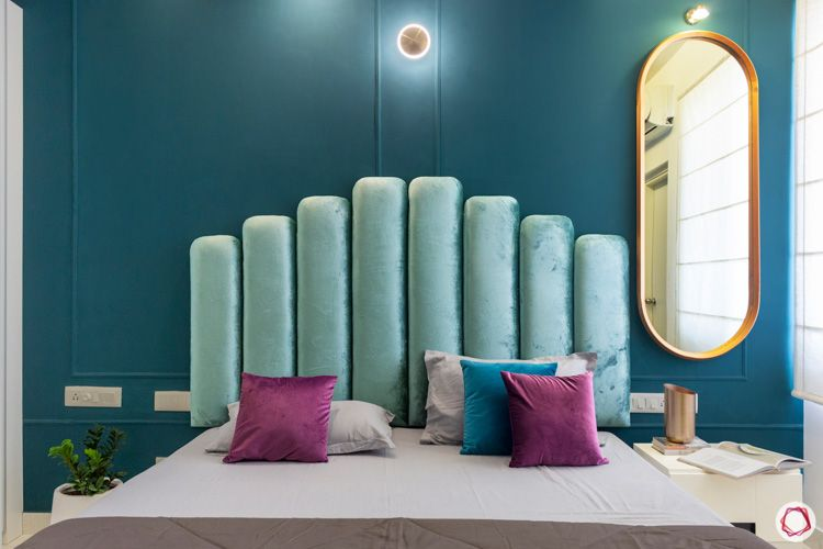 green velvet headboard-oval mirror designs-blue wall-wall trim