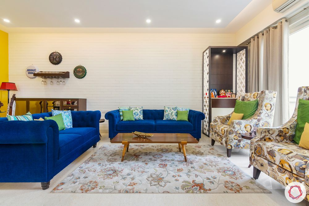 3 bhk interior design-living room-blue sofa-jaali pooja unit-white exposed brick wallpaper-centre table-bar unit