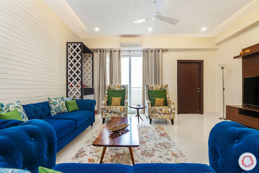 living room-blue sofa-jaali pooja unit-white exposed brick wallpaper-centre table-window